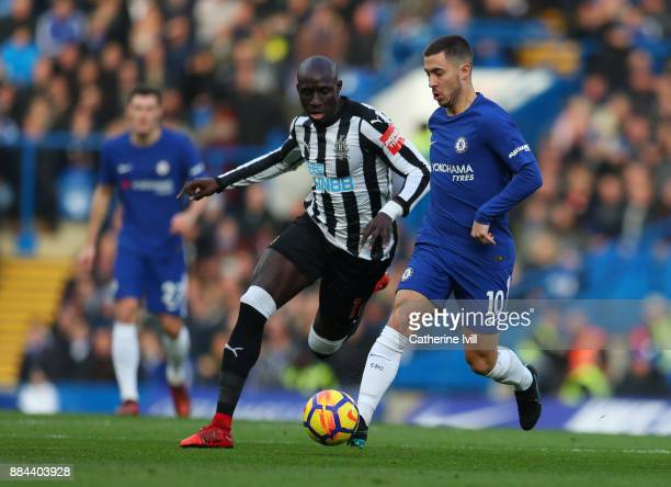 Eden Hazard of Chelsea is challenged by Mohamed Diame of Newcastle United during the Premier League match between Chelsea and Newcastle United at...