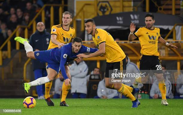Eden Hazard of Chelsea is challenged by Romain Saiss and Ryan Bennett of Wolverhampton Wanderers during the Premier League match between...