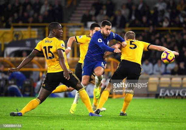 Eden Hazard of Chelsea is challenged by Ryan Bennett and Willy Boly of Wolverhampton Wanderers during the Premier League match between Wolverhampton...