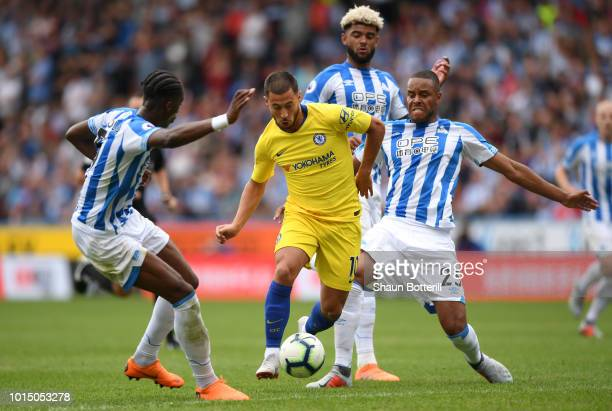 Eden Hazard of Chelsea is challenged by Terence Kongolo of Huddersfield Town and Mathias Zanka Jorgensen of Huddersfield Town during the Premier...