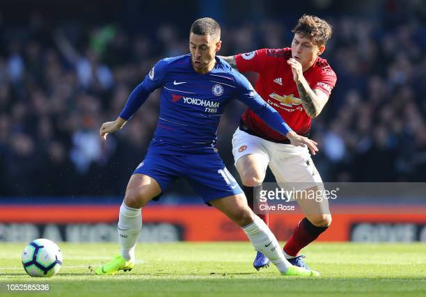 Eden Hazard of Chelsea is challenged by Victor Lindelof of Manchester United during the Premier League match between Chelsea FC and Manchester United...