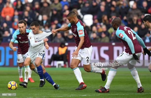 Eden Hazard of Chelsea is challenged by Winston Reid of West Ham United during the Premier League match between West Ham United and Chelsea at London...