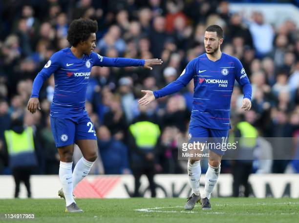 Eden Hazard of Chelsea is congratulated by teammate Willian of Chelsea after scoring his team's first goal during the Premier League match between...
