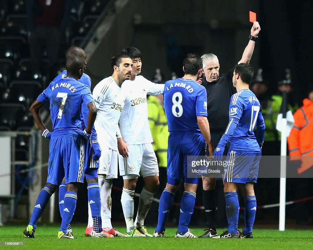 Eden Hazard of Chelsea (R) is sent off by referee Chris Foy after kicking a ball boy during the Capital One Cup Semi-Final Second Leg match between Swansea City and Chelsea at Liberty Stadium on January 23, 2013 in Swansea, Wales.