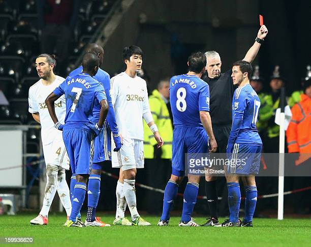Eden Hazard of Chelsea is sent off by referee Chris Foy after kicking a ball boy during the Capital One Cup SemiFinal Second Leg match between...