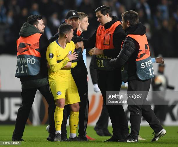 Eden Hazard of Chelsea is surrounded by stewards after a fan invades the pitch after the UEFA Europa League Round of 32 First Leg match between Malmo...