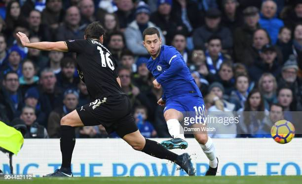 Eden Hazard of Chelsea passes the ball under pressure from Aleksander Dragovic of Leicester City during the Premier League match between Chelsea and...