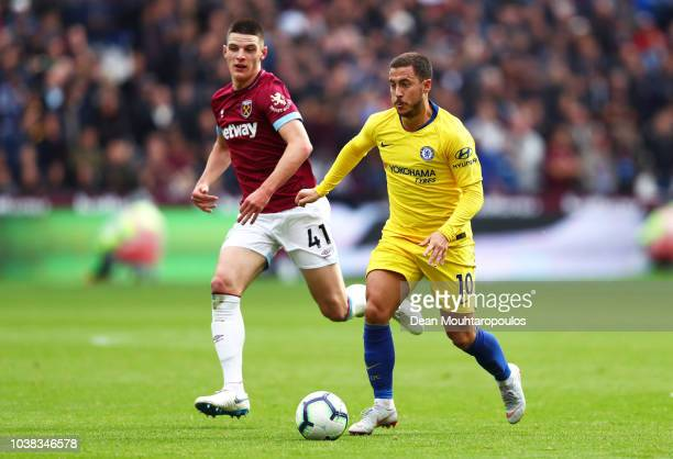 Eden Hazard of Chelsea runs with the ball under pressure from Declan Rice of West Ham United during the Premier League match between West Ham United...