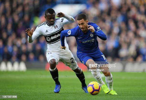Eden Hazard of Chelsea runs with the ball under pressure from Jean Michael Seri of Fulham during the Premier League match between Chelsea FC and...