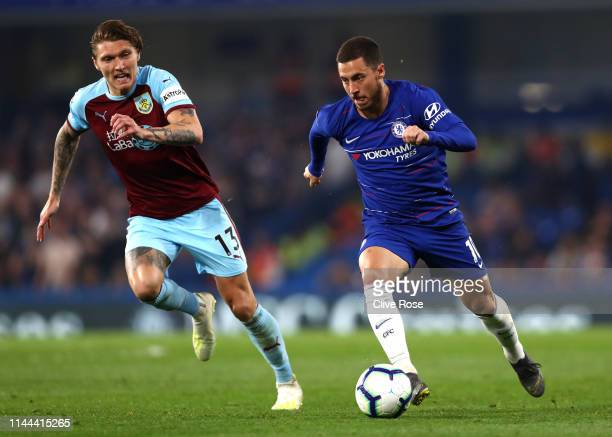 Eden Hazard of Chelsea runs with the ball under pressure from Jeff Hendrick of Burnley during the Premier League match between Chelsea FC and Burnley...