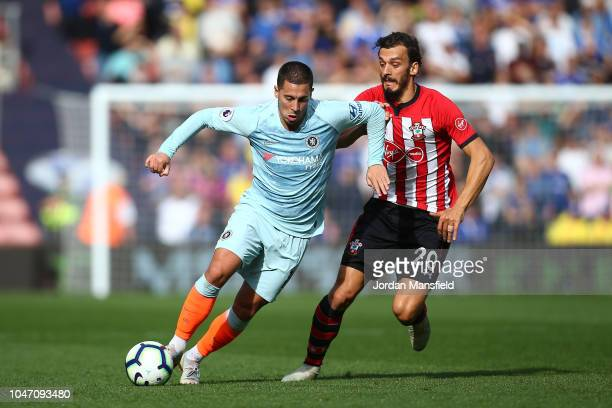 Eden Hazard of Chelsea runs with the ball under pressure from Manolo Gabbiadini of Southampton during the Premier League match between Southampton FC...