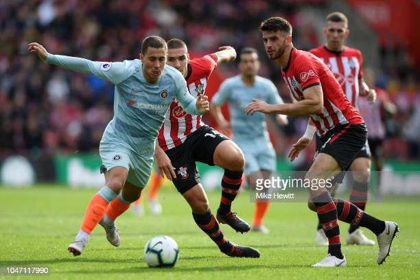 Eden Hazard of Chelsea runs with the ball under pressure from Oriol Romeu of Southampton during the Premier League match between Southampton FC and...