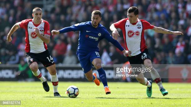 Eden Hazard of Chelsea runs with the ball under pressure from Oriol Romeu of Southampton and PierreEmile Hojbjerg of Southampton during the Premier...