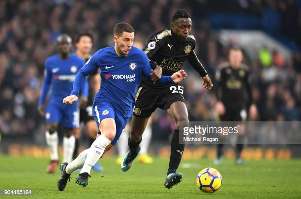 Eden Hazard of Chelsea runs with the ball under pressure from Wilfred Ndidi of Leicester City during the Premier League match between Chelsea and...