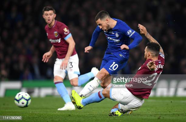 Eden Hazard of Chelsea scores his team's first goal as he is challenged by Ryan Fredericks of West Ham United during the Premier League match between...
