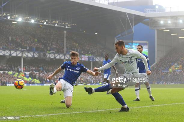 Eden Hazard of Chelsea shoots as Jonjoe Kenny of Everton attempts to block during the Premier League match between Everton and Chelsea at Goodison...