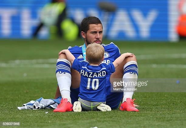 Eden Hazard of Chelsea sits on the pitch with his son