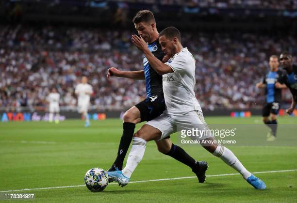 Eden Hazard of Real Madrid battles for possession with Brandon Mechele of Club Brugge during the UEFA Champions League group A match between Real...