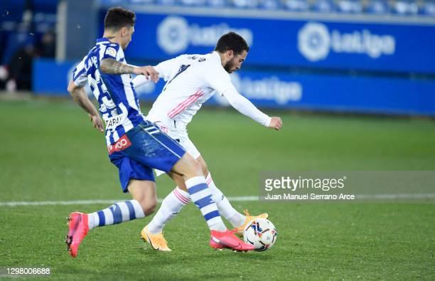 Eden Hazard of Real Madrid scores their team's third goal past Ximo Navarro of Deportivo Alaves during the La Liga Santander match between Deportivo...