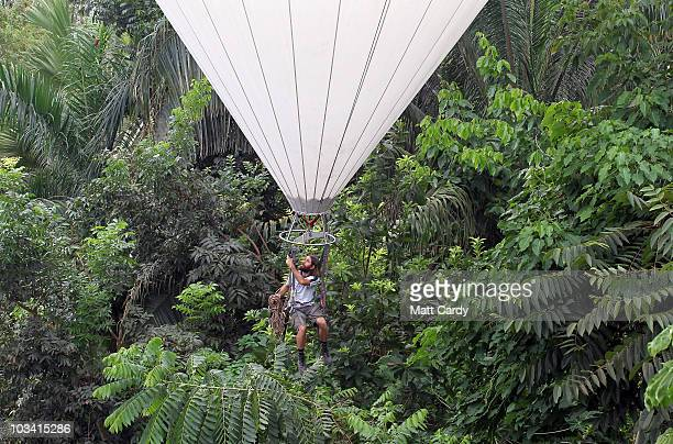 Eden horticulturist John Nichol throws down ropes as he moves above the canopy of the Rainforest Biome using a helium balloon at the Eden Project on...
