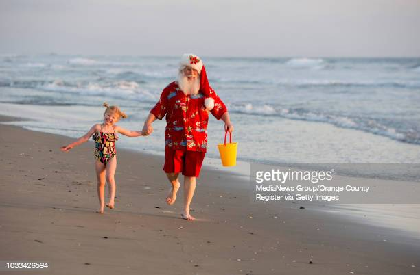 Eden Wenger left prances along the shore with Santa Claus during the Orange County Register's annual Christmas Day cover photo shoot in Huntington...