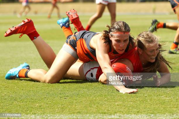 Eden Zanker of the Demons is tackled as she takes a mark by Pepa Randall of the Giants during the round five AFLW match between the Greater Western...