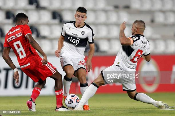 Edenilson of Internacional competes for the ball with Braian Ojeda and Richard Ortiz of Olimpia during a match between Olimpia and Internacional as...