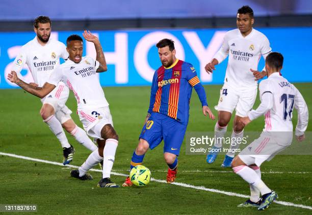 Eder Militao of Real Madrid competes for the ball with Lionel Messi of FC Barcelona during the La Liga Santander match between Real Madrid and FC...
