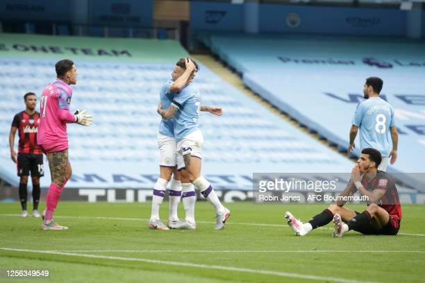 Ederson and John Stones congratulate teammate Nicolas Otamendi of Manchester City after he blocks Dominic Solanke of Bournemouth's goal bound shot...
