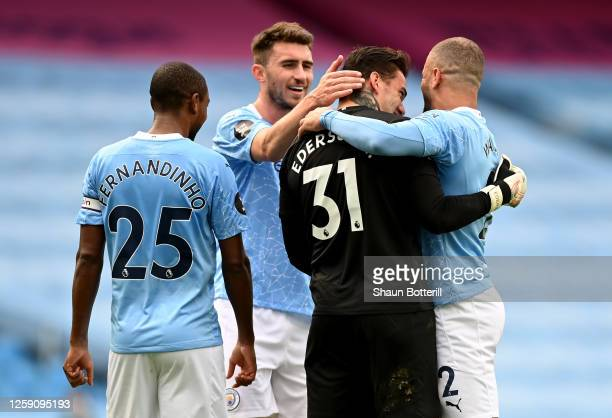 Ederson, Kyle Walker, Fernandinho and Aymeric Laporte all of Manchester City celebrate after the Premier League match between Manchester City and...