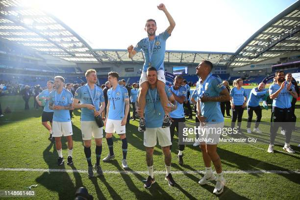 Ederson lifts Bernardo Silva of Manchester City as they celebrate winning the Premier League title following the Premier League match between...