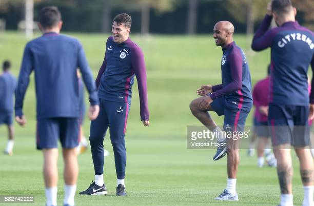 Ederson Moraes and Fabian Delph react during training at Manchester City Football Academy on October 18 2017 in Manchester England