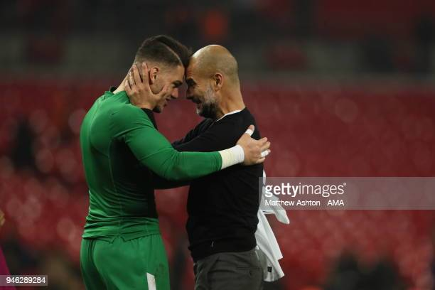Ederson Moraes of Manchester City and Manchester City manager Pep Guardiola during the Premier League match between Tottenham Hotspur and Manchester...