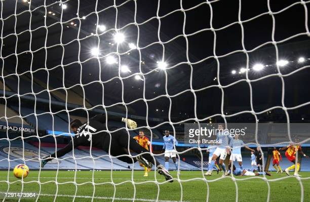 Ederson of Manchester City dives for the ball as Ruben Dias of Manchester City scores an own goal for West Bromwich Albion's first during the Premier...