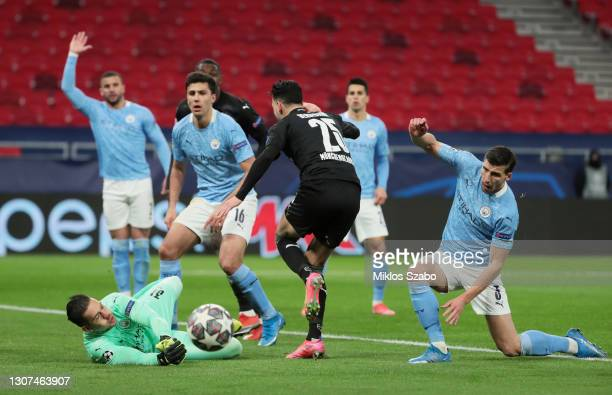 Ederson of Manchester City makes a save from Ramy Bensebaini of Borussia Moenchengladbach as Ruben Dias of Manchester City looks on during the UEFA...