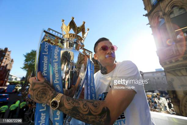 Ederson of Manchester City poses with the Premier League trophy on a parade bus during the Manchester City Teams Celebration Parade on May 20 2019 in...