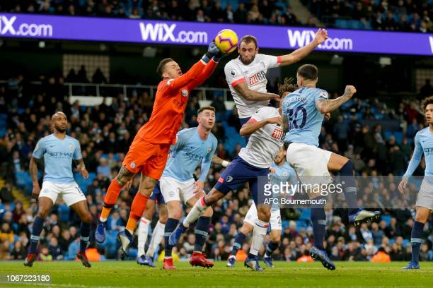 Ederson of Manchester City punches clear of Steve Cook of Bournemouth during the Premier League match between Manchester City and AFC Bournemouth at...