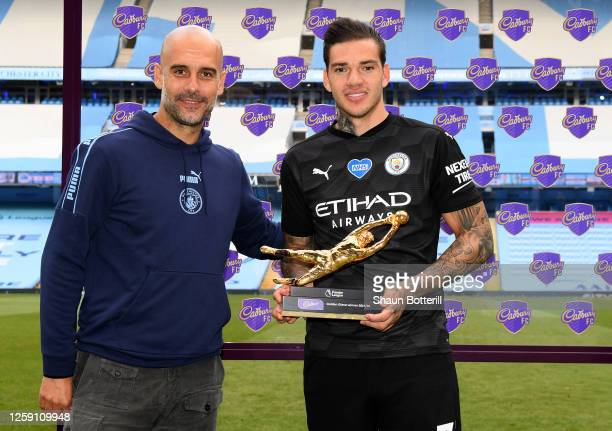 Ederson of Manchester City receives the Golden Glove Award from Pep Guardiola, Manager of Manchester City after the Premier League match between...