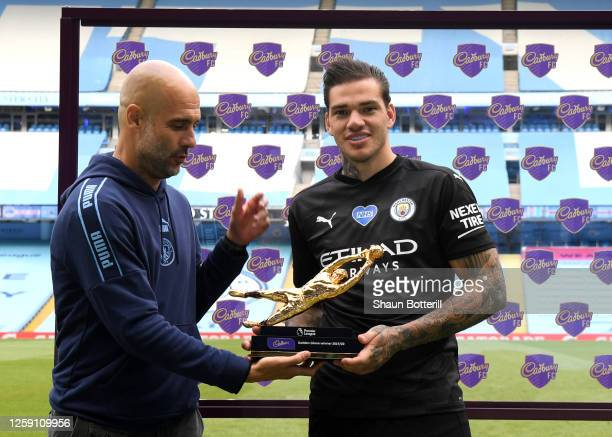 Ederson of Manchester City receives the Golden Glove Award from Pep Guardiola Manager of Manchester City after the Premier League match between...