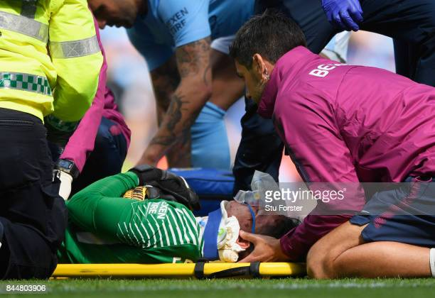 Ederson of Manchester City receives treatment from the medical team during the Premier League match between Manchester City and Liverpool at Etihad...