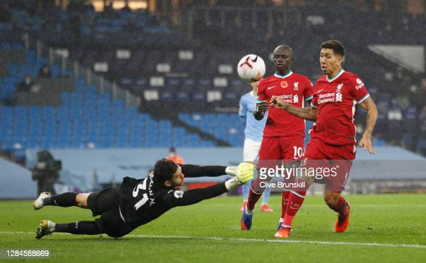 Ederson of Manchester City saves a shot from Roberto Firmino of Liverpool during the Premier League match between Manchester City and Liverpool at...