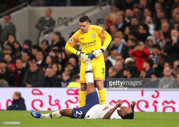 Ederson of Manchester City stretches out the leg of Steven Bergwijn of Tottenham Hotspur after going down for cramp during the Premier League match...