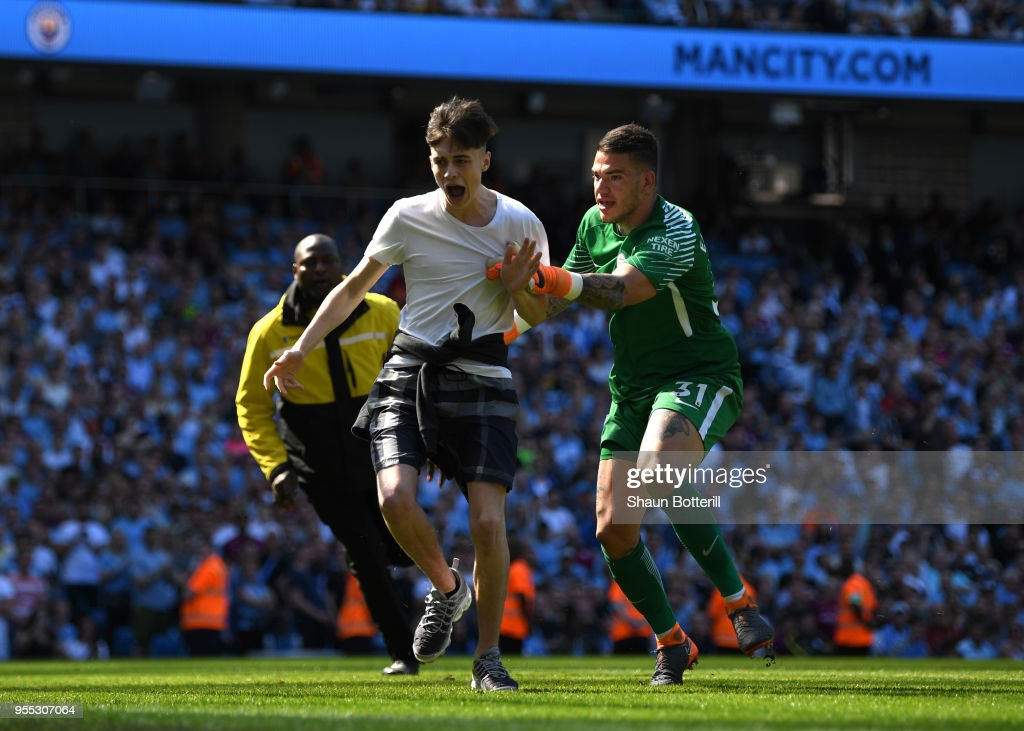 Ederson of Manchester City tackles a pitch invador during the Premier League match between Manchester City and Huddersfield Town at Etihad Stadium on May 6, 2018 in Manchester, England.