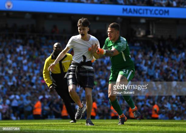 Ederson of Manchester City tackles a pitch invador during the Premier League match between Manchester City and Huddersfield Town at Etihad Stadium on...