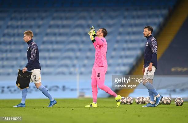 Ederson of Manchester City takes a moment of reflection as he and teammates Kevin De Bruyne and Ruben Dias of Manchester City make their way out to...