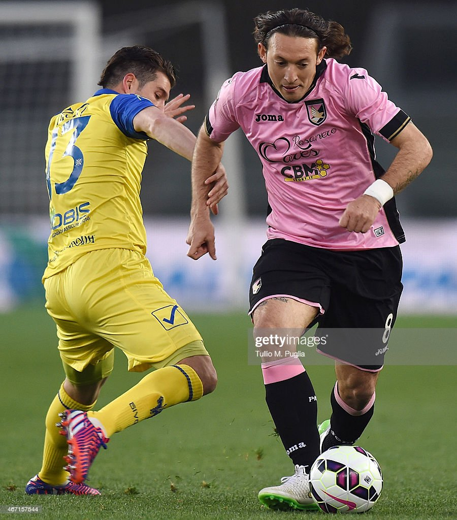 Edgar Barreto (R) of Palermo holds off the challanger from Mariano Izco of Chievo during the Serie A match between AC Chievo Verona and US Citta di Palermo at Stadio Marc'Antonio Bentegodi on March 21, 2015 in Verona, Italy.
