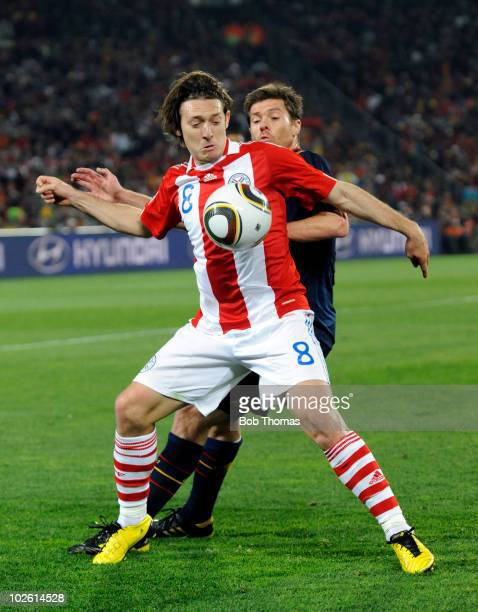 Edgar Barreto of Paraguay challenged by Xabi Alonso of Spain during the 2010 FIFA World Cup South Africa Quarter Final match between Paraguay and...