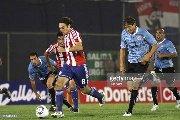 Edgar Barreto of Paraguay fights for the ball with Sebastian Eguren of Uruguay during the match between Paraguay and Uruguay as part of the first...