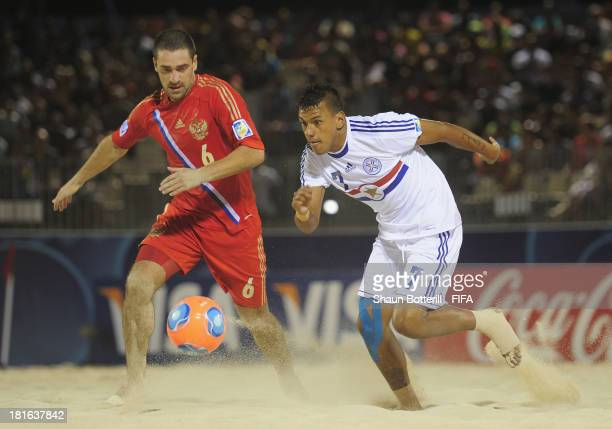 Edgar Barreto of Paraguay is challenged by Dmitrii Shishin of Russia during the FIFA Beach Soccer World Cup Tahiti 2013 Group D match between Russia...