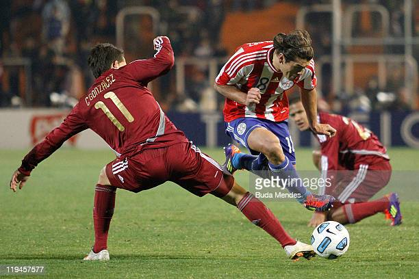Edgar Barreto of Paraguay struggles for the ball with Cesar Gonzalez of Venezuela during a match as part of Copa America 2011 Semifinal at Malvinas...